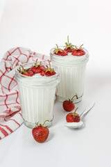 Dessert yogurt and strawberry layers in a glass on a red striped napkin on a white background