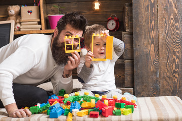 Family fun time. Happy dad and son look through small plastic window and door. Father and blond kid play with colorful plastic blocks on sofa