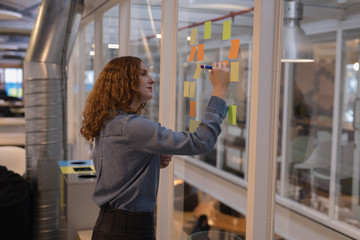 Female executive writing on sticky note