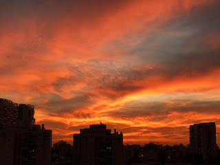 Sunset in the city with stunning colorful magic clouds. Spring sky with red clouds and roofs view.