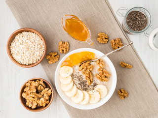 healthy breakfast - oatmeal with nuts, bananas, chia, jam,  top view, close up