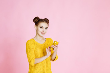 portrait of young attractive girl on pink background in Studio. Blonde in a yellow sweater with hair collected in the hair, lively talking on the phone, dials a message or views news on the Internet
