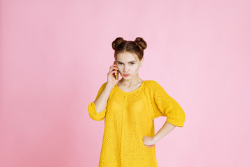 portrait of young attractive girl on pink background in Studio. Blonde in a yellow sweater with hair collected in the hair, lively talking on the phone. upset by the bad news, frowning and sad.