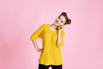 portrait of young attractive girl on pink background in Studio. Blonde in a yellow sweater with hair collected in the hair, lively talking on the phone, looking into the camera and enjoys