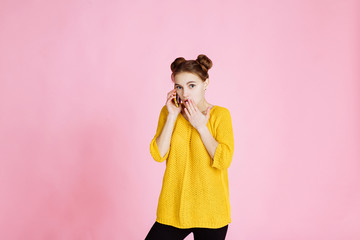 portrait of young attractive girl on pink background. Blonde in a yellow sweater, lively talking on the phone. surprised by unexpected news, expresses shock, fright or surprise.
