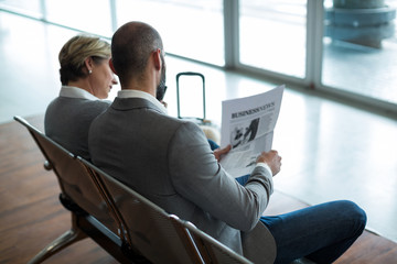 Businesspeople reading newspaper in waiting area