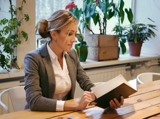 Young businesswoman sitting at table in coffee shop and reading book