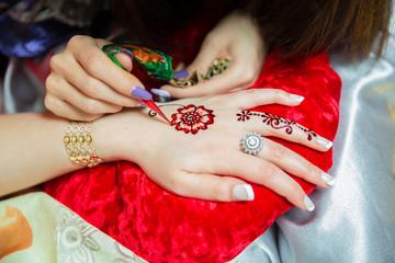 Henna design tattoo. Women applying roses henna tattoo on women hands. Woman draws mehendi on the hands . Artist applying henna tattoo on bride hands.