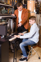 Glad boy and father deciding on synthesizer