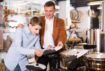 teenager and father deciding on drum unit in musical shop