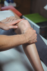 Physiotherapist giving physical therapy to the knee of a female patient