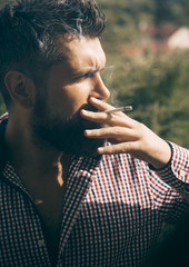 unhealthy lifestyle and bad habit of guy with addiction. man smoking cigarette. young bearded hipster with beard and moustache on serious face smoking cigarette outdoor. hairdresser and barbershop