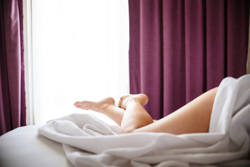 crossed woman legs on bed in bedroom.