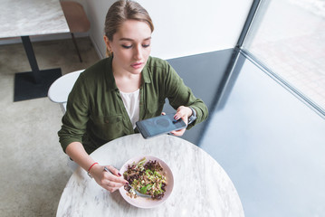 A pretty girl makes a photo of a salad in a restaurant. The blogger picks up food on the table near the window