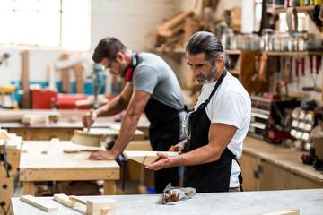 Carpenter checking a wooden plank