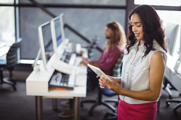 Female sound engineer in studio using digital tablet