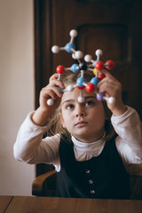 Girl looking through molecule model