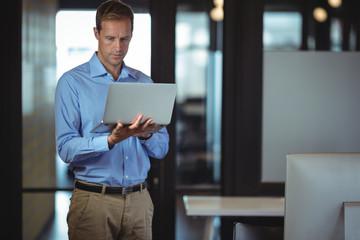 Thoughtful businessman using laptop