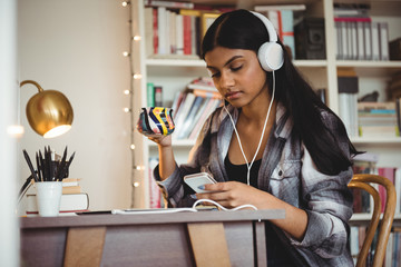 Woman listening to music on digital tablet while having coffee