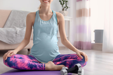 Young pregnant woman doing exercises at home
