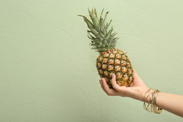 Woman holding pineapple on color background, closeup