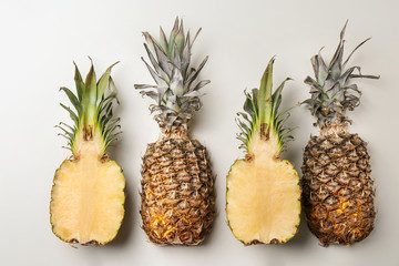 Fresh pineapples on light background, flat lay