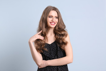 Portrait of young woman with long beautiful hair on color background