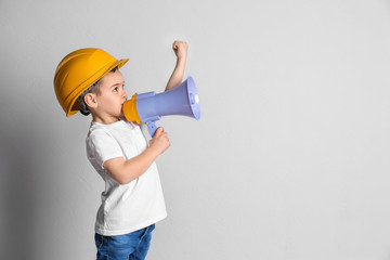 Adorable little boy in hardhat with megaphone on light background