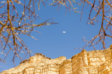 Fototapete - White zeppelin floating above desert mountain cliffs.
