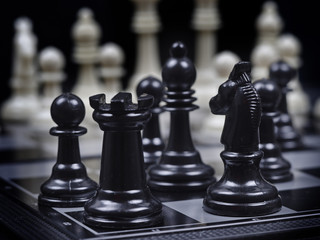 black chess pieces on white chess pieces background