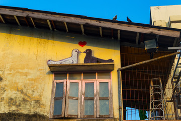 Two drawn pigeons with red love heart on the graffiti. Romantic streetart in Phuket, Thailand. Real doves on the building roof. Blue and yellow.