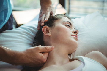 Male physiotherapist giving neck massage to female patient