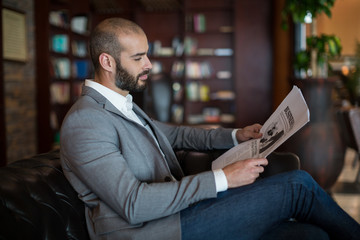 Businessman reading newspaper in waiting area