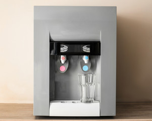 Modern water cooler with glass on table indoors
