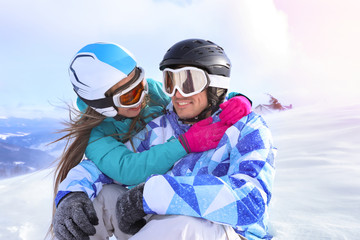 Happy couple at snowy ski resort. Winter vacation