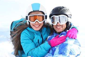 Happy couple at snowy ski resort. Winter vacation