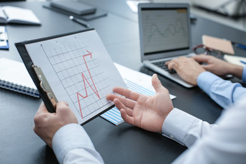 Man working at table in office, closeup. Forex concept