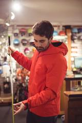 Man holding a ski pole in shop