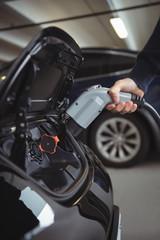 Man charging car at electric vehicle charging station
