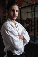Portrait of man in karategi standing with arms crossed