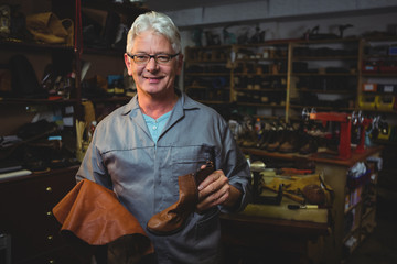 Portrait of smiling cobbler with shoe standing in workshop