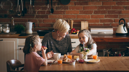Mother and kids having breakfast at table