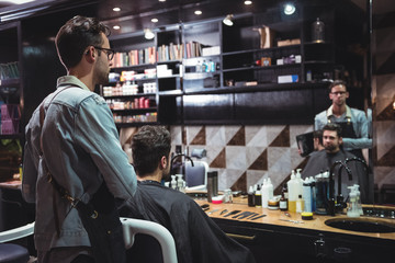 Barber showing man his haircut in mirror