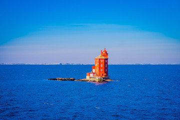 Outdoor view of the red lighthouse on the Norwegian sea over a rock