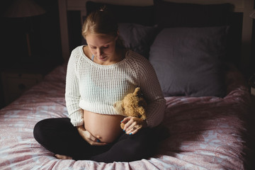 Pregnant woman holding teddy bear in bedroom