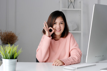 Young asian businesswoman showing okay hand gesture sign and smiling with happiness at office desk, woman working in casual home office lifestyle concept