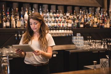 Female bartender using digital tablet