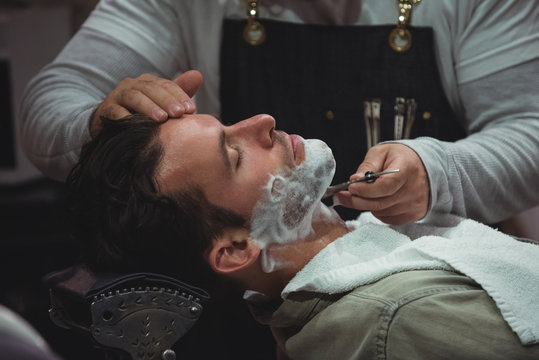 Barber shaving man beard with razor in saloon