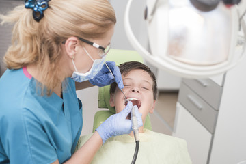 Boy with perfect teeth at the dentist doing teeth whitening - oral hygiene health care concept