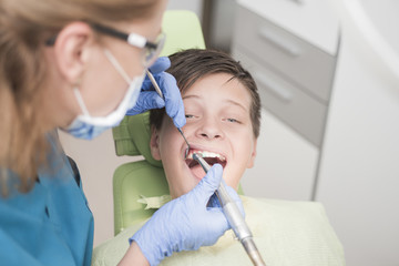 Boy whitening his teeth at the dentist - oral hygiene health care concept